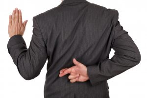 Swearing an oath with fingers crossed behind back concept for dishonesty or business fraud